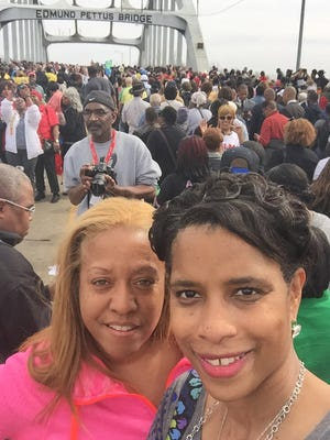 Greenville residents Dawn Hilton-Williams, left, and Rhonda Rawlings stand amid thousands of people at Edmund Pettus Bridge commemorating the 50th anniversary of the Selma marches for freedom.