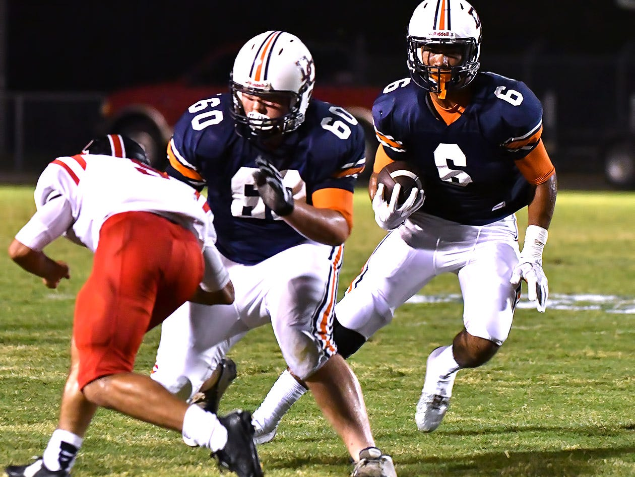 Dickson County's Darian Burns picks up a block from Noah Chapdelaine. Dickson County vs Rossview. Friday, Sept. 23, 2016 at Dickson County.