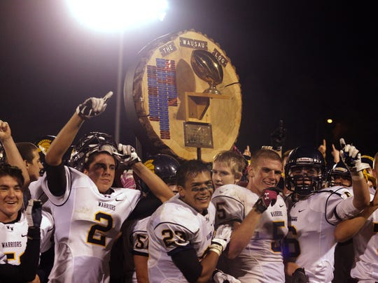 Members of the Wausau West football team hoist the Wausau Log trophy after defeating Wausau East in 2013.