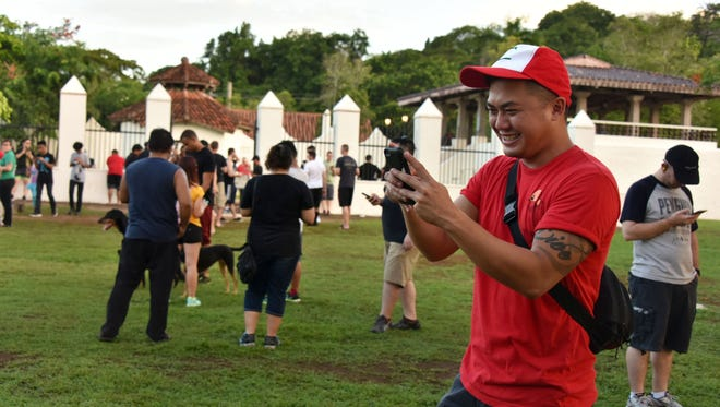 Frank Candaso, 31, of Barrigada plays Pokémon Go on his cellphone at the Plaza de España in the evening hours of on July 12.