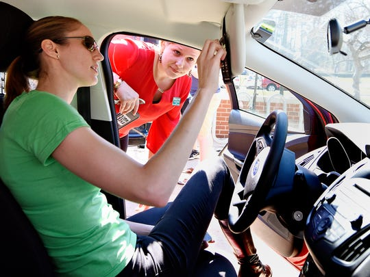 Evva Comans, left, with Zipcar, shows York College Director of Student Activities and Orientation Sara Goodwin where the gas card is kept for fueling the car as York College launches their partnership with Zipcar on the patio of Iosue Student Union at the college in York, Wednesday, March 9, 2016. Dawn J. Sagert photo