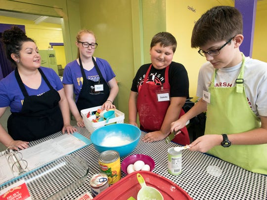 Ryan Philson, right, tries his hand baking while attending