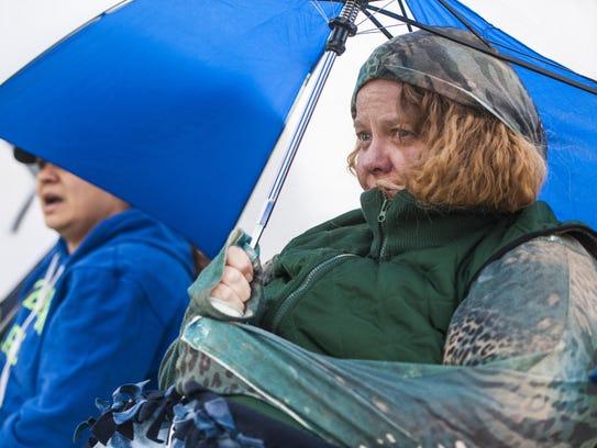 Stephanie Cummings huddles underneath an umbrella while