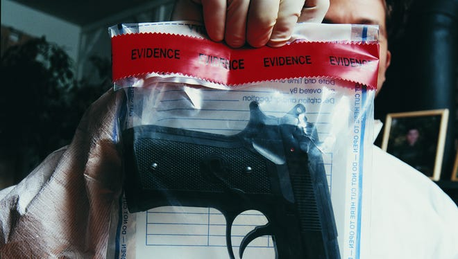 Forensic scientist holding an evidence bag with a gun inside.
