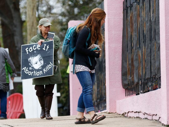 Anti-abortion sidewalk counselors Beka Tate, foreground, and Laura Duran, call out to a woman entering the Jackson Women's Health Organization's clinic, the only facility in the state that performs abortions, March 20, 2018, in Jackson, Miss.