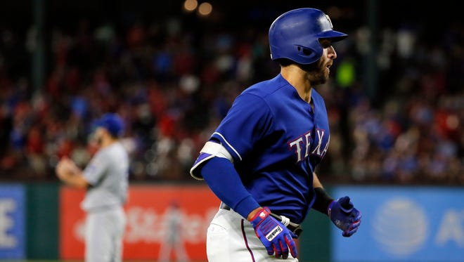 Texas Rangers' Joey Gallo jogs home after hitting a solo home run off Kansas City Royals starting pitcher Nathan Karns, rear, during the fifth inning of a baseball game in Arlington, Texas.