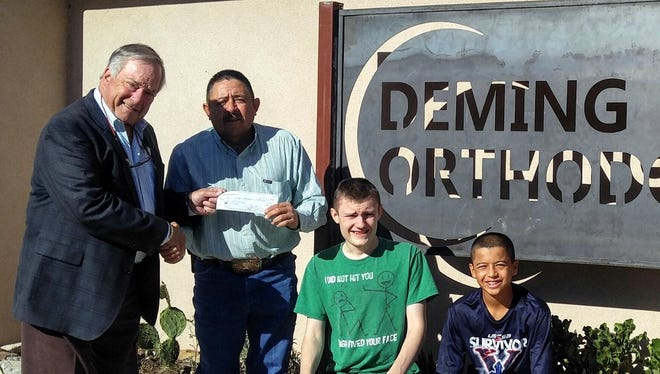 Dr. Bob Brewka, left, presented a check to Red Mountain Middle School welding/woods shop teacher Jerry Montes as eighth-grade welding students Herron and Fernando Milo look on.