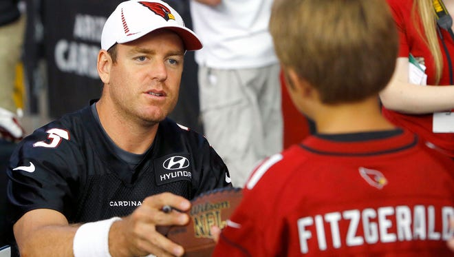 Arizona Cardinals' Carson Palmer signs a football for Kailob Bartrau during an autograph session of Fan Fest 2013 at the University of Phoenix Stadium in Glendale.