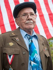 96-year-old World War II veteran Salvatore C. DeSanto raises the American flag outside his home in Oaklyn. DeSanto was laid off from his part-time job this year after 31 years and he wants to find another part-time but is having difficulty getting one because of his age.