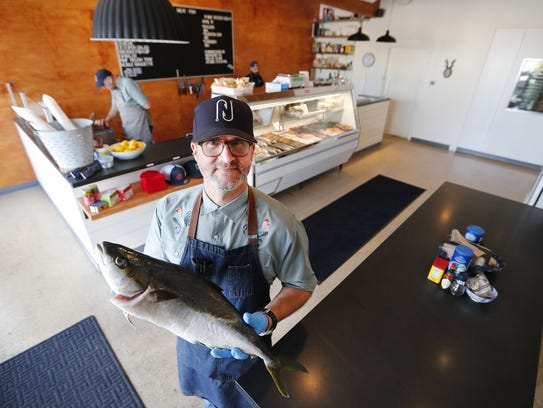 Christopher Nelson holds a hiramasa at Nelson's Meat + Fish in Phoenix on April 10, 2018.