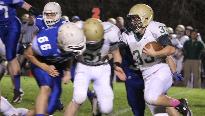 Regis running back Paden Reynolds (33) tries to turn the corner behind the block of teammate Taylor Silbernagel (21) in the Rams' game against Central Linn on Friday, Oct. 31, 2014.
