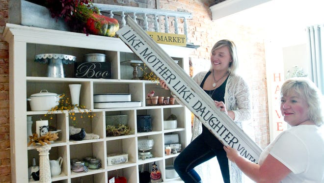 """Jordan Wester, on step ladder, and her mother Jada Wester prepare to open their vintage home furnishings business in downtown Howell. The store, located on State Street, will be called """"Like Mother Like Daughter Vintage Treasures."""""""