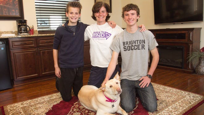 Holly Purdy, R.N., center, has opened Blue Heron Pond Adult Foster Care in Green Oak Township, and moved into the adjoining residence with her sons 13-year-old Jack Purdy, left, and 16-year-old Noah Purdy and two dogs. Cameo, a shepherd/lab mix pictured with the family, will serve at the facility as a therapy dog.