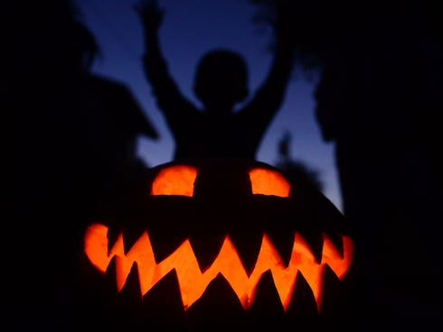 Children play behind a pumpkin carved and lit for Halloween, on Oct. 30, 2013, in Monterey Park, Calif.