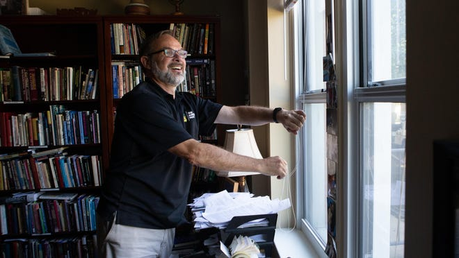 """The Rev. Jim Congdon, pastor of Topeka Bible Church, opens the blinds to his office Friday afternoon while discussing the """"In the Spirit of Reconciliation"""" public prayer gathering he is helping to host Sunday at the Capitol along with the Rev. Clarence Newton, pastor of New Life Baptist Church."""