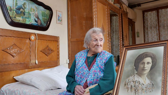 Emma Morano, then 116, sits in her apartment next to a picture depicting her when she was young in Verbania, Northern Italy.