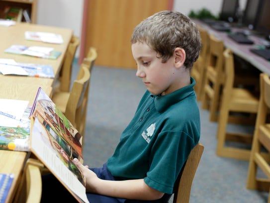 Alic Lanclos reading in the library at Sts. Leo-Seton
