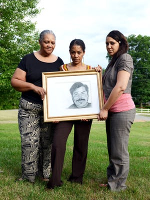 Family members of Walter Rodney Bowman from left, Alma Bowman, wife, stand with a picture of Bowman with daughters Vallie Evita Bowman and SoRay Bowman Woods at a family's home Thursday evening.