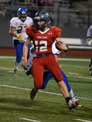 Quarterback Brett Traeger carries the ball for Kennedy on Saturday night.