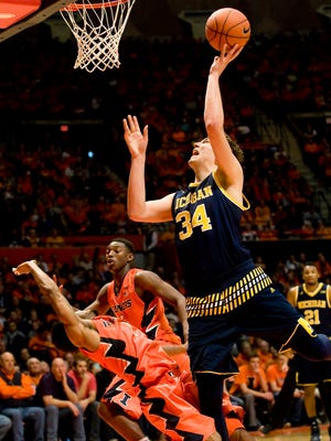 Michigan forward Mark Donnal (34) shoots over Illinois guard Jaylon Tate (1) in the second half of U-M's win Wednesday at the State Farm Center.