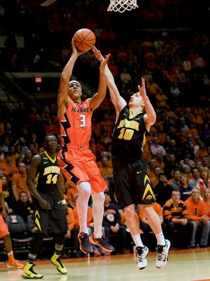 Mike Gesell bothers the shot of Illinois' Khalid Lewis in Iowa's 77-65 win.
