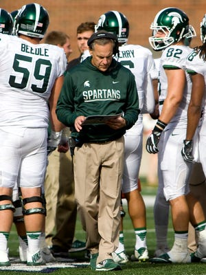Michigan State head coach Mark Dantonio consults his play chart during the fourth quarter against the Illinois Saturday at Spartan Stadium.