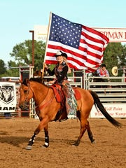 Miss Rodeo Montana Lindsay Garpestad of Simms, here carrying the American flag at the Wild Horse Stampede in Wolf Point, traveled to 25 Montana Circuit rodeos last year. The C.M. Russell High graduate's reign as Miss Rodeo Montana ends this weekend.
