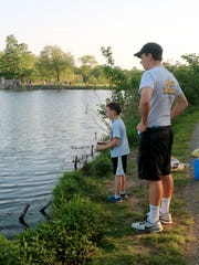 Ryan Polizzi, 18, watches as his cousin, Liam O'Dell, 7, casts his line into the lake at Verona Park in May 2017.