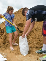 Morgan and Landon Sellers filling sandbags in preparation