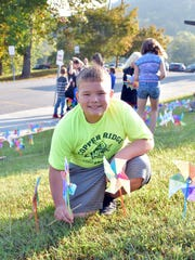 Fifth-grade student Branson Peters places pinwheels