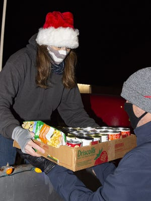 Andrea Pfeifer, left, donates food collected at Auld Lang Syne Antiques to the Christmas Cruise for a Cause on Saturday night.