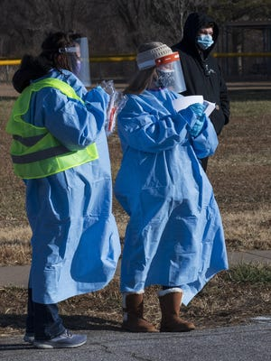 Health care workers clothed in personal protective equipment distribute information at Sunday's free COVID-19 test collection sponsored by Salina Family Healthcare Center and the Salina Regional Health Center at Bill Burke Park on Sunday. The COVID-19 test were saliva based, rather than the nasal method.