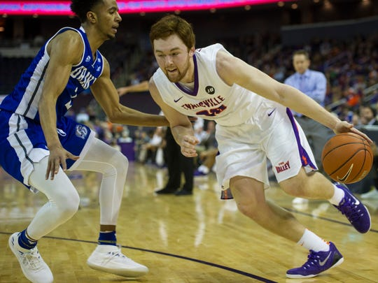 University of Evansville's Noah Frederking (30) drives on Drake's Jalen Gibbs (2) at the Ford Center on Saturday, Jan. 27, 2018. The Purple Aces defeated the Bulldogs 77-73.