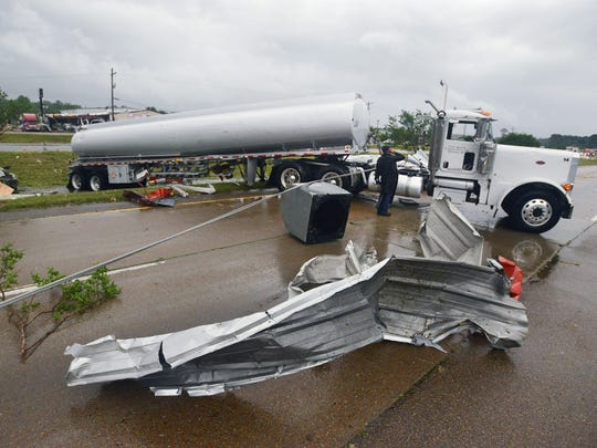 An 18-wheeler and numerous strips of sheet metal block the south-bound lanes of U.S. 49 in Richland  after a tornado ripped through the area late Monday afternoon.  According to the truck's driver (inspecting cab), he was alerted to the tornado in time to pull to the shoulder, lock his brakes and curl into the floor of his cab before the rig was spun 90 degrees amid a hail-storm of flying debris when the tornado passed.  Despite the ordeal, he escaped unharmed.
