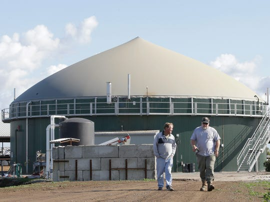 Arlan Van Leeuwen (left) and Arlin Van Groningen, co-owners of the new New Hope Dairy, converse as they walk near 1 million gallon storage tank used to hold raw cow manure, at the dairy in Galt, CA.