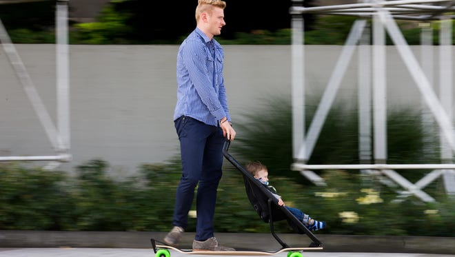 Father and son roll on a Longboard Stroller.