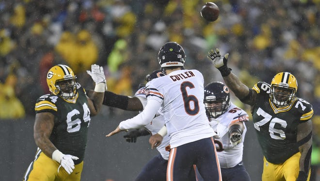 Chicago Bears quarterback Jay Cutler (6) throws under pressure from Green Bay Packers defensive end Mike Pennel (64) and defensive end Mike Daniels (76) at Lambeau Field on Nov. 26.