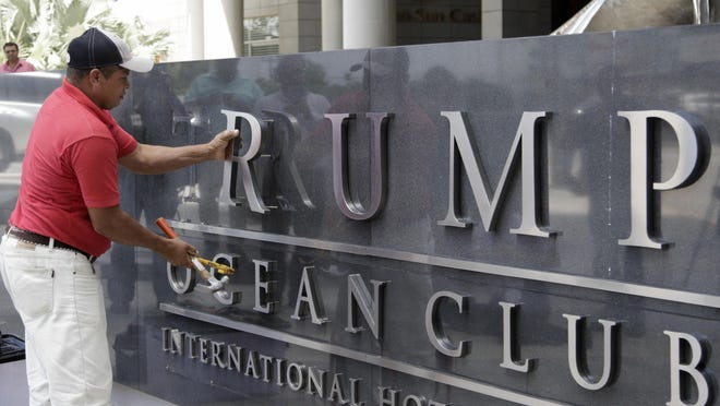 In this March 5, 2018 file photo, a man removes the word Trump, off a marquee outside the Trump Ocean Club International Hotel and Tower in Panama City. The luxury hotel that used to bear the Trump name has formally been rebranded on Tuesday, Sept. 25, after a bitter dispute over control. The 70-story, sail-shaped tower is now the JW Marriott.