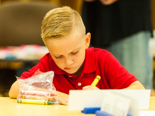 Winslow kindergartner Bryce Lofton colors on the first day of school at Winslow Elementary on Wednesday, September 6.