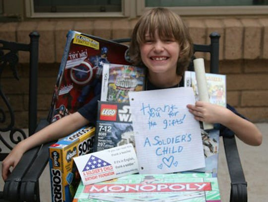 A Soldier's Child birthday recipient holds a card of