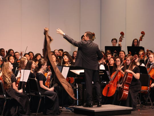 "Richard Ballinger, director of the Oslo and Storm Grove Middle School orchestras, throws his Jedi Master cape to second violin section leader Jasmine Schutt as Ballinger begins to conduct the opening ""String Wars"" medley."