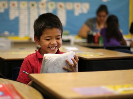 Marko Lokee, 7, a first-grade student at Sacred Heart School in Waterloo, laughs with classmates. Lokee is one of many students from Burma who attend the school.