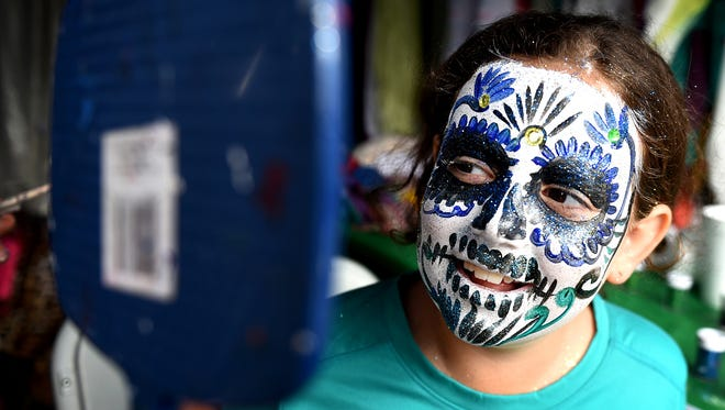 Breana Yodis, 9, looks at her painted face created by artist Jose Vera during a Dia de los Muertos celebration on Saturday, Oct. 24, 2015 at Cheekwood.