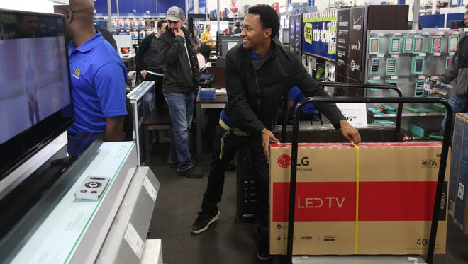 Best Buy Inventory Associate Zevin Martin assists in getting more televisions to the floor inside the Nashville Best Buy during Black Friday on Thanksgiving Day, Nov. 24, 2016.