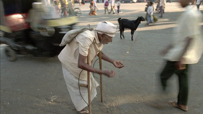 Pedestrians walk by an elderly beggar on the streets of Bangalore, India.