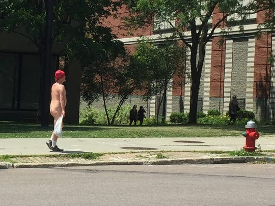 A man clad in a bandanna, socks and shoes walks north on Pine Street toward Burlington Town Center in this file photo from 2016. The man declined to identify himself.