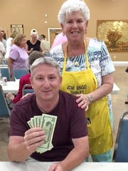 Bingo Committee member Shirley Posner hands Robbie Taylor of Marco Island his big prize at JCMI's Monday Night Bingo.