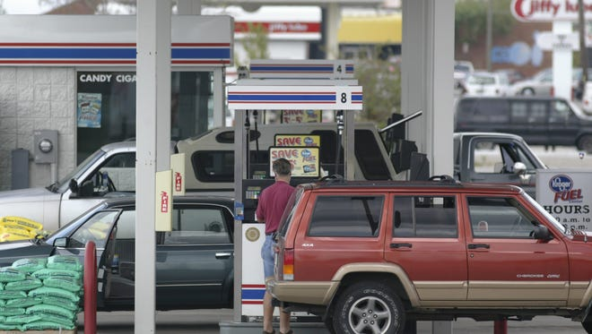 Customers fill up their vehicles at a gas station.