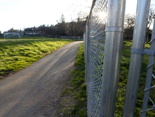 Fencing and gates surround the soccer fields behind