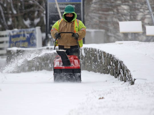 Workers clear snow from sidewalks along Pennsylvania Ave. during one of Delaware's recent snowstorms.